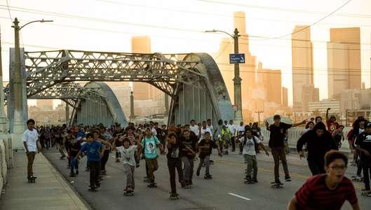 A massive group of skateboarders skates across a bridge in Los Angeles