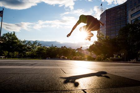 Skateboarder flips board through the sun