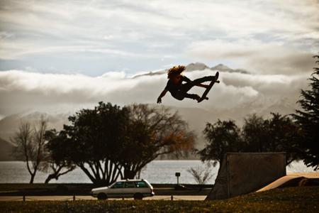 Shaun White flies through air on skateboard in front of mountains