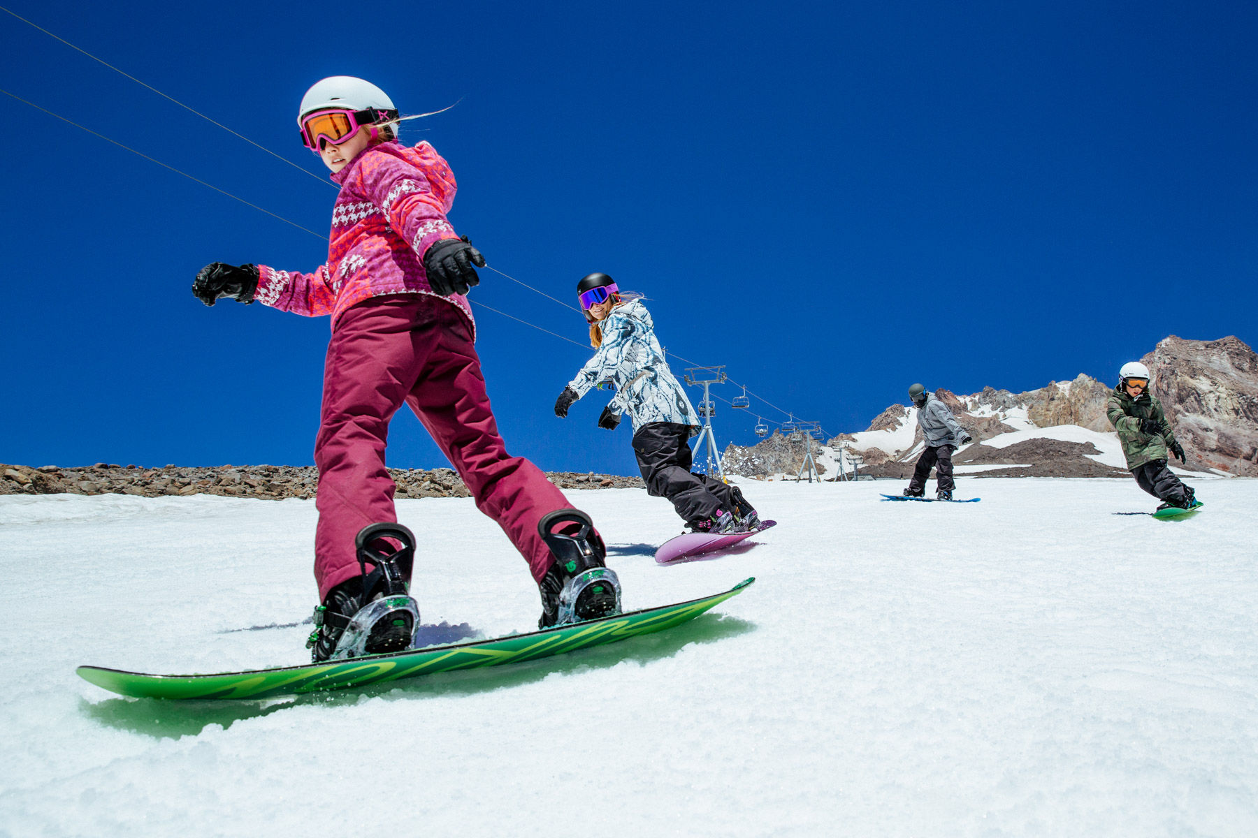 Family Riding Snowboards Down Mountain