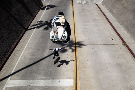 A skateboarder skates down street with a VW Bug following him