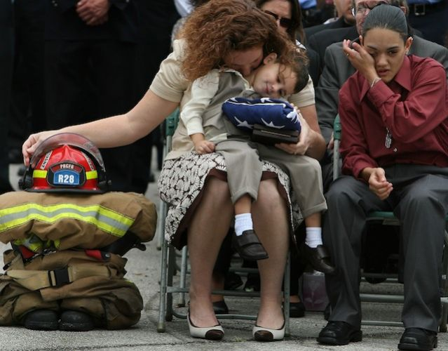 Fallen firefighter's wife and children grieve during his memorial service.
