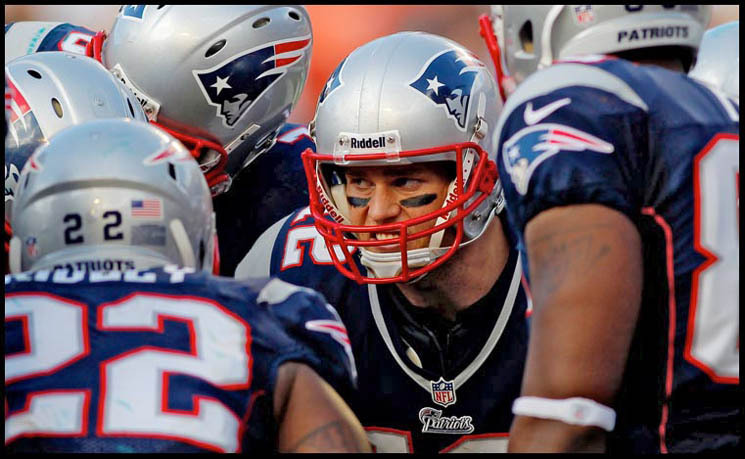 New England Patriots quarterback TOM BRADY shows his intensity in the huddle.