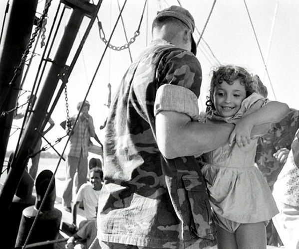 A young Cuban girl is carried of a crowded boat by a U.S. Marine.