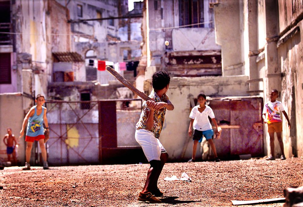 Kids play with a paper ball and stick bat between decaying buildings in Cuba.