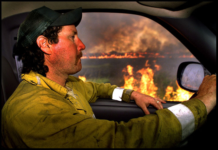 Firefighter drives through brush fires in South Florida.