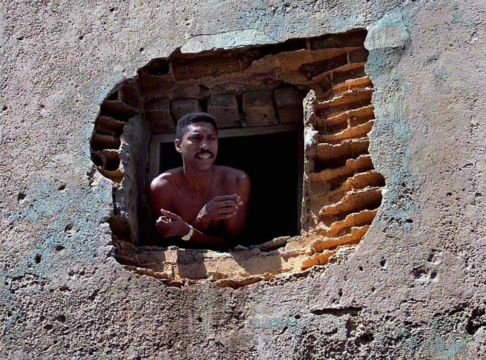 Man watches kids play stickball from decay  building