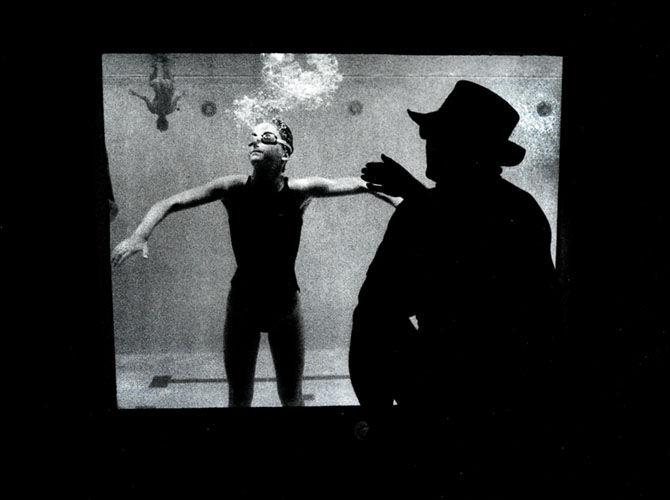 Coach instruts his swimmer through an underwater window.