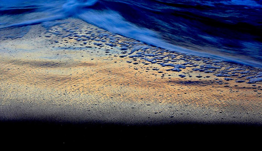 OCEAN at Sunrise: blue foam over golden sand.