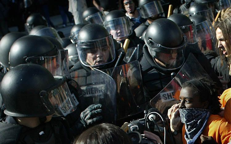 A protester confronts police in riot gear during the FTAA summit in Miami.