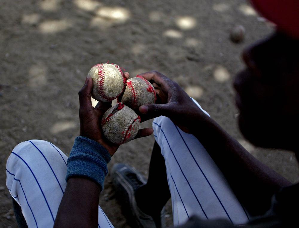 Dominican holds tattered baseballs.