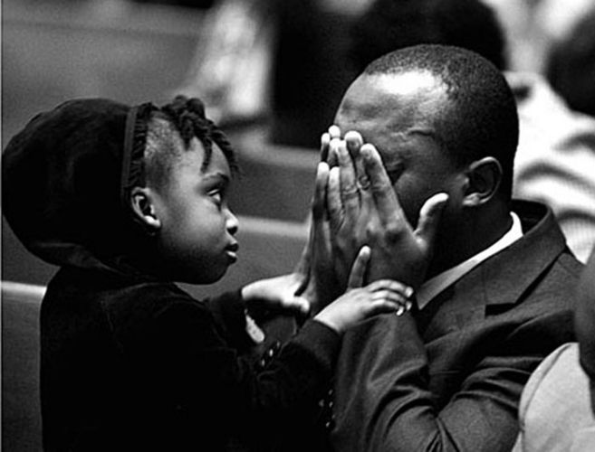 Daughter comforts her father during a vigil for Haitian's lost during a hurricane.