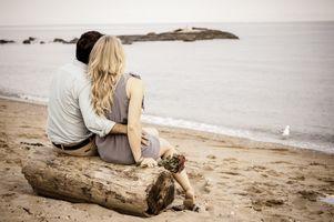 couplesittingondriftwoodatbeach.jpg
