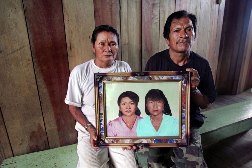 Miguel Mashumar and Maria Claudia Antuash sit with a portrait of their deceased daughters Rosa and Maria Graciela at their home on the Via Auca.