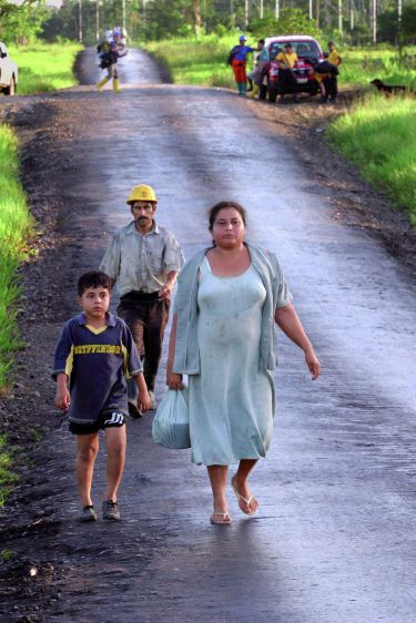 A mother and son are joined by oil workers as they walk on a road covered with crude oil outside the town of Shushufindi.