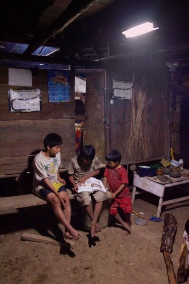 Kichwa boys read a school book at their home in Sarayaku with light provided by a newly installed solar power system.