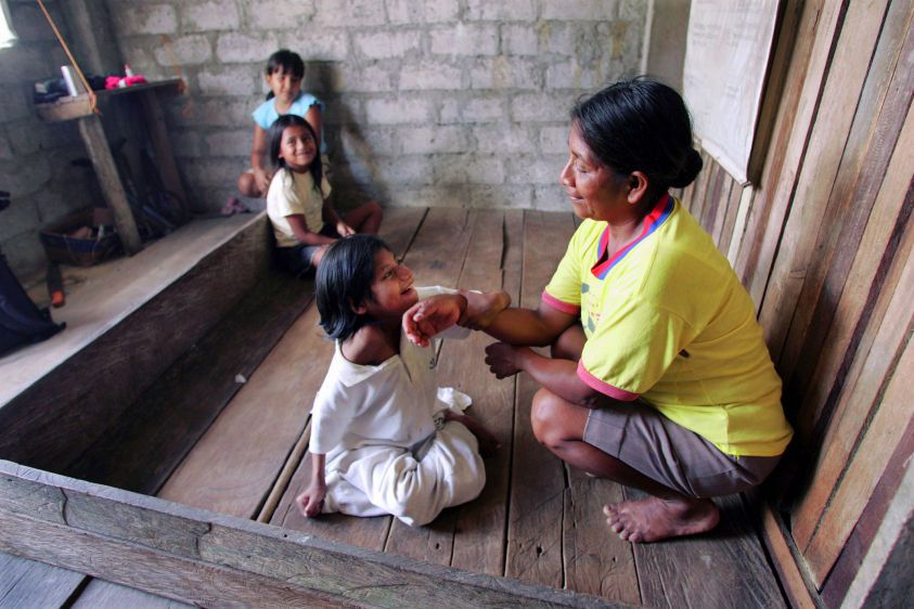 Fifteen-year-old Myra Chicaiza sits with her mother Rosa Mercedes on the floor of their home in Dureno.
