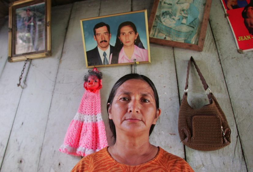 At her home in La Andina, Amanda Armijos, sister-in-law of Juana Apolo, stands in front of a photo of herself and husband Saul Apolo who died of stomach cancer.