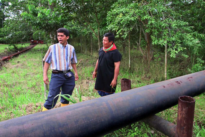 Pablo Fajardo (L), lead Ecuadoran attorney on the Chevron case, speaks with Cofan indigenous leader Emergildo Criollo at an oil facility in the Guanta oil fields. The plant was built by Texaco (now Chevron) on Cofan ancestral territory.