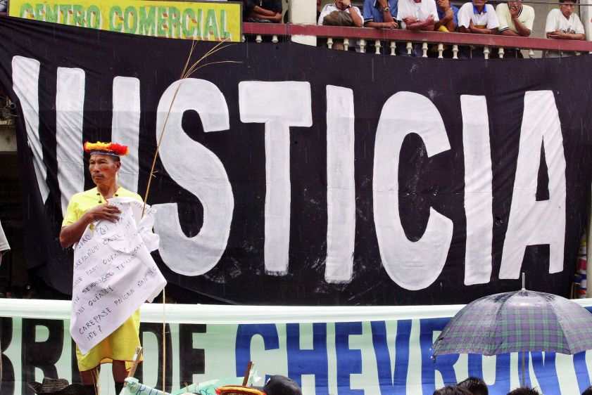 "A Secoya elder stands in front of a banner reading ""Justice"" during a demonstration at the start of the trial against Chevron (formerly Texaco) in Lago Agrio."