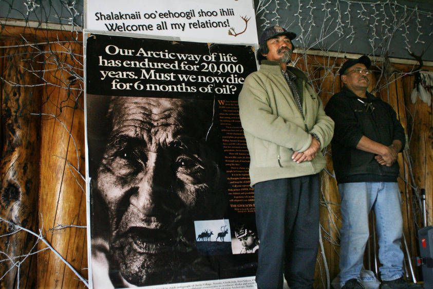"Gwich'in stand near poster at opening of ""Celebration of Land and Life""."