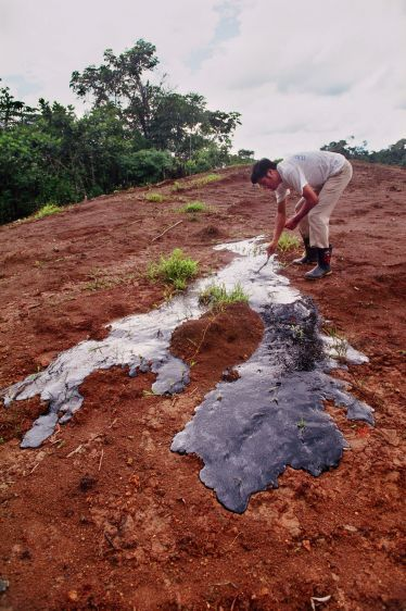 Oil rises to the surface from a waste pit covered with dirt near Coca in 1993.