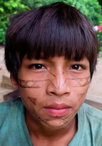 Kichwa youth Braulio Ikiami, 14, with his face pain­ted to resemble a boa constrictor outside his home in Sarayaku.