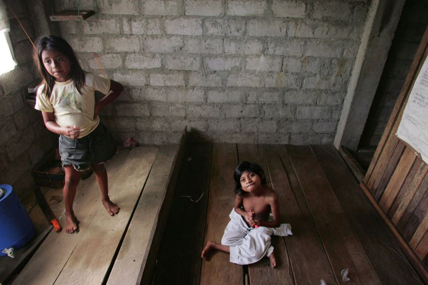 With her eight-year-old sister Alexandra Raquel at left, fifteen-year-old Myra Chicaiza sits on the floor of her home in Dureno.