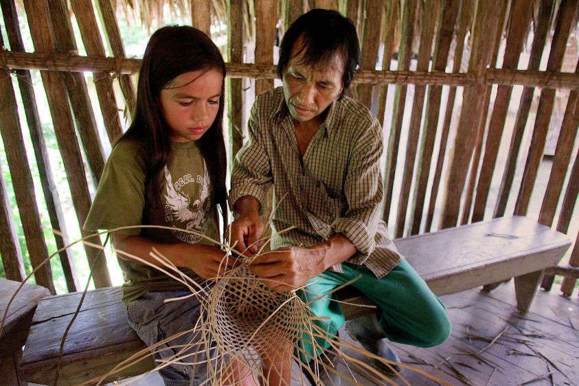 Bolivar Shiwango (right) shows 11-year-old Rasu how to weave a basket during an artisan class at Rasu's school in Sarayaku. The Kichwa teach their children basket weaving, ceramic making and other artisan skills to make sure their cultural traditions con