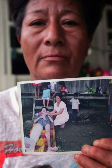Dolores Morales, at her home in Sacha, holds a photo of her nineteen-year-old son Pedro who died of cancerous tumors.