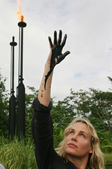 With an oil flare burning in the background, actress and environmental activist Daryl Hannah looks at her hand dripping with crude oil from a waste pit left by Texaco in the Guanta oil fields.