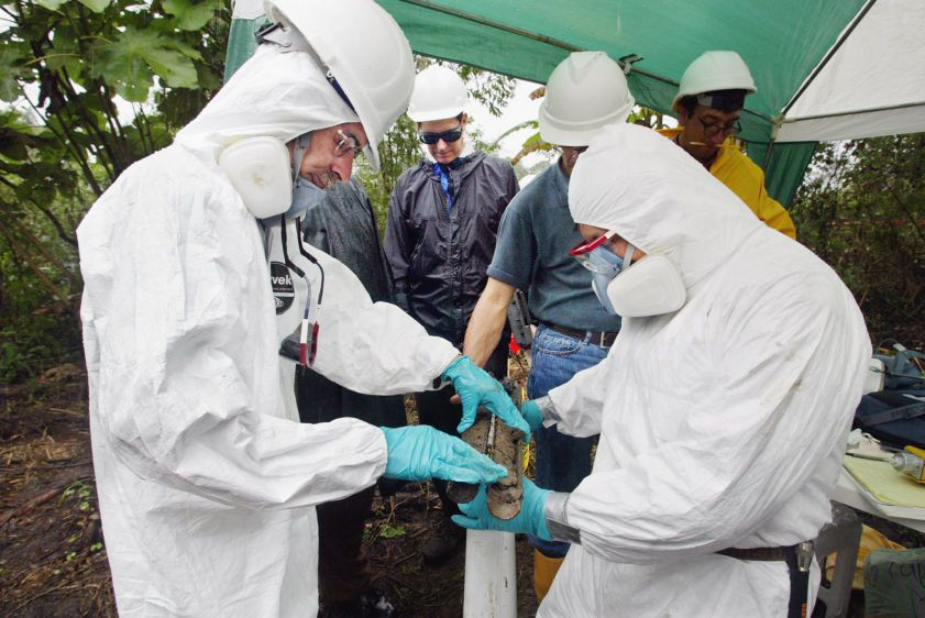As Chevron technical expert John Connors (C) looks on, technicians in haz mat suits check a soil sample for evidence of crude oil during judicial inspections at an old Texaco well site near the town of Sacha.