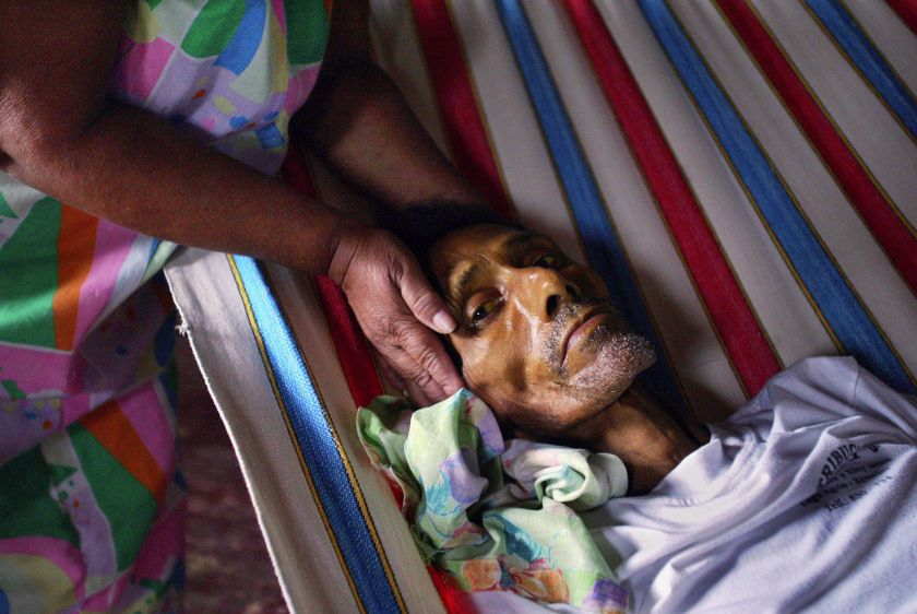 Luz Maria Marin holds the head of her husband Angel Toala one day before he died of stomach cancer in his home in Shushufindi.