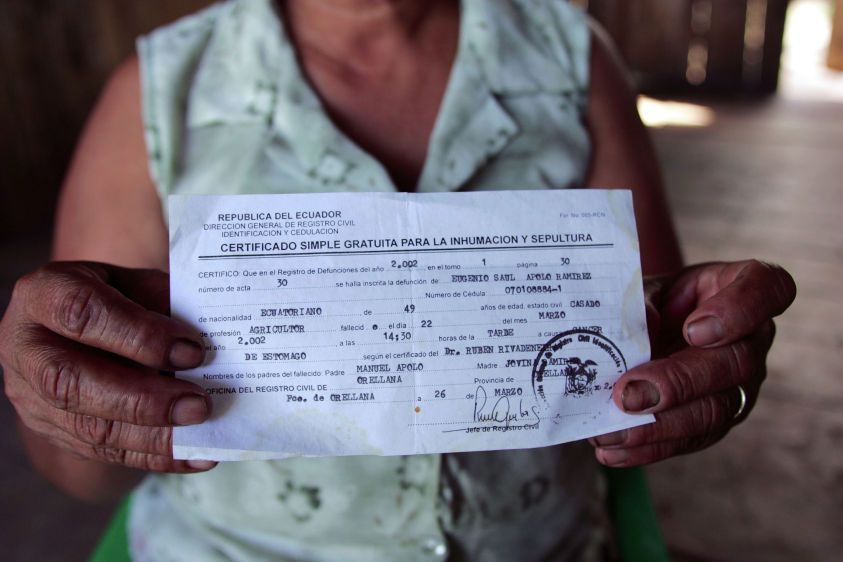 At her home in La Andina, Amanda Armijos holds the death certificate of her husband Saul Apolo which lists stomach cancer as the cause of death.