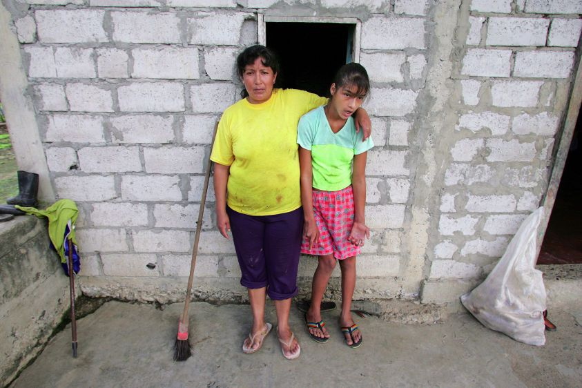 Carmen Guaman (L) with her fourteen-year-old daughter Veronica, who suffers from birth defects, at their home in La Primavera.