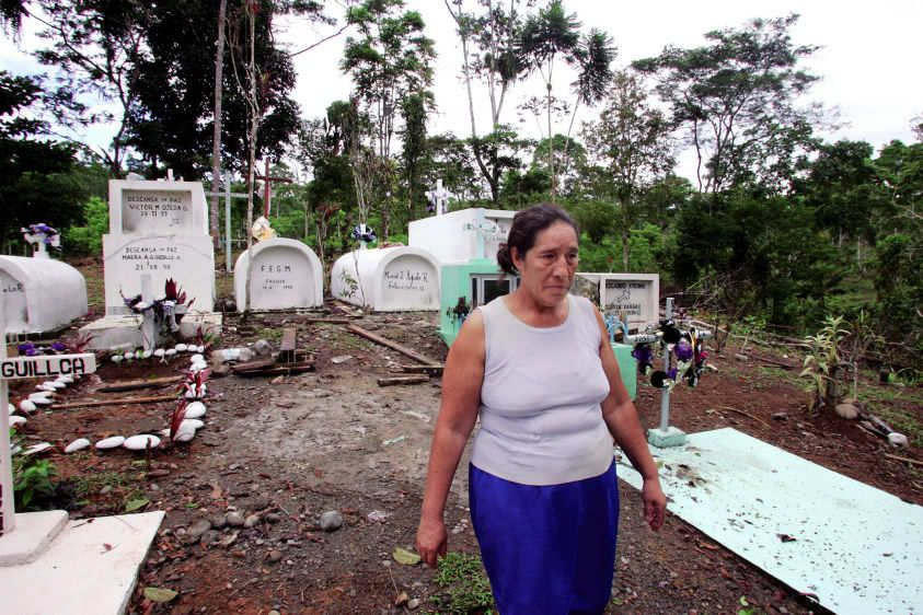 Juana Apolo walks out of a cemetary in La Andina where her father, brother and sister are buried, all of whom died of cancer.