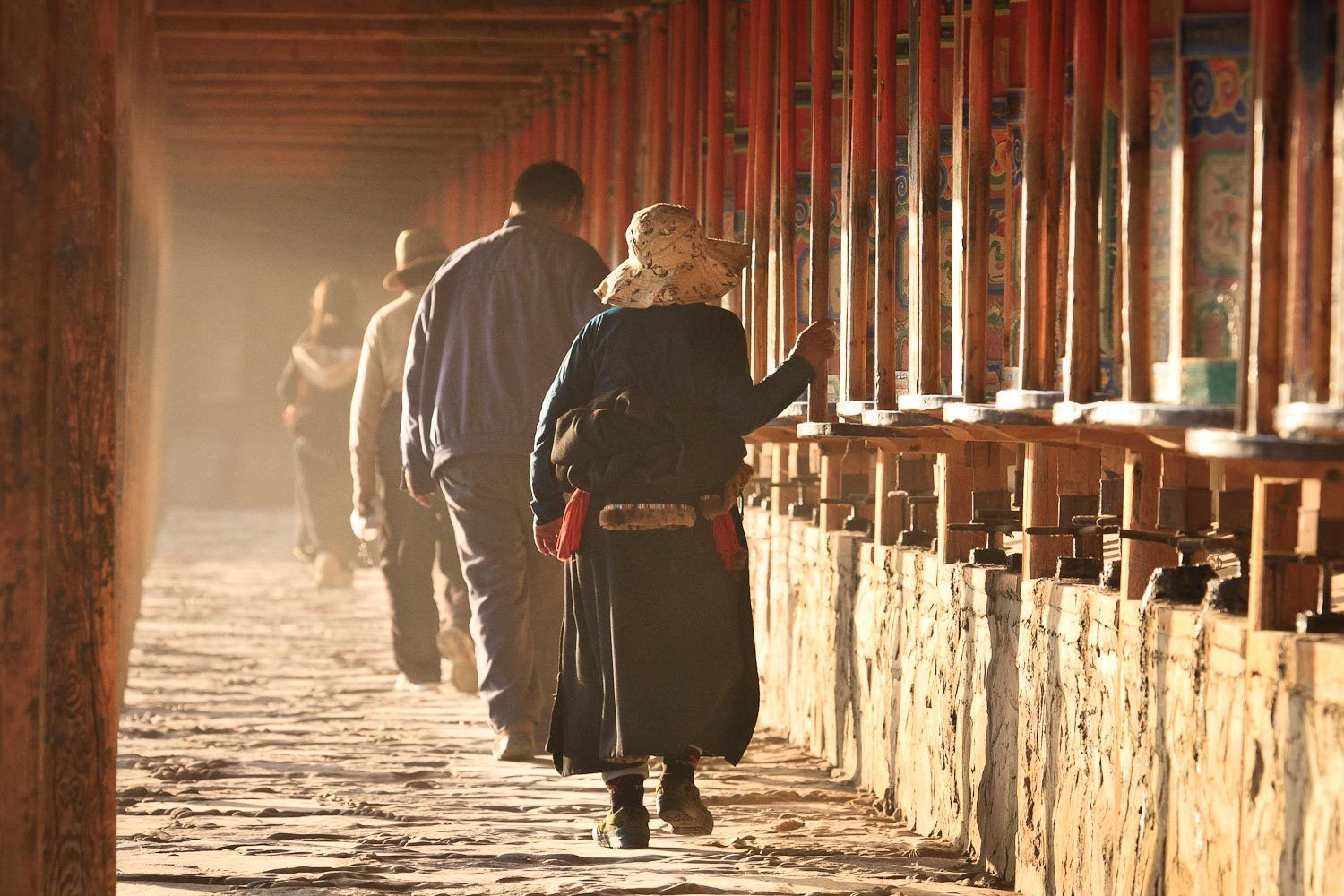 Devotees turning prayer wheels on the kora surrounding Labrang Monastery, Xiahe, Gansu, China.