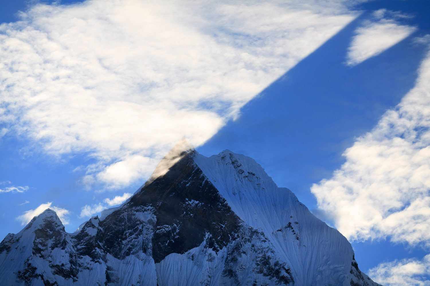 A  shadow of Mt Machhapuchhare (the Fish Tail) projected on to a layer of cloud at sunrise, Annapurna Base Camp trek, Nepal.