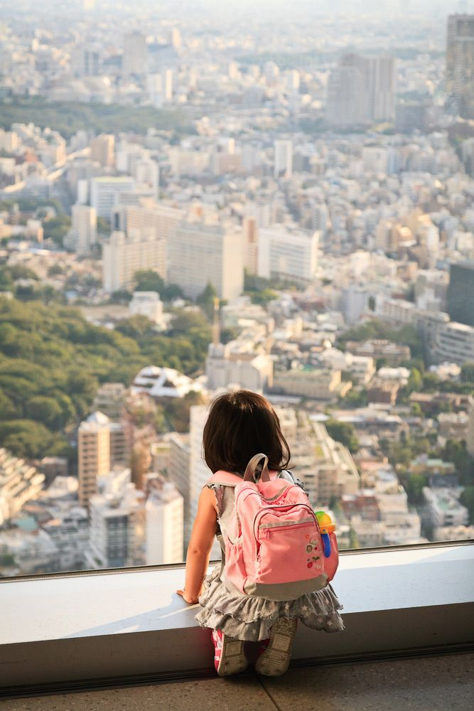 A young girl gazing at the buildings of Tokyo from the Mori Tower, Roppongi Hills, Tokyo, Japan.