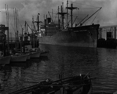 """Ship """"China Victory"""" And Fishing Boats, San Francisco Waterfront, San Francisco Bay, California."""