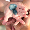 Image of child's sandy hand with seashells