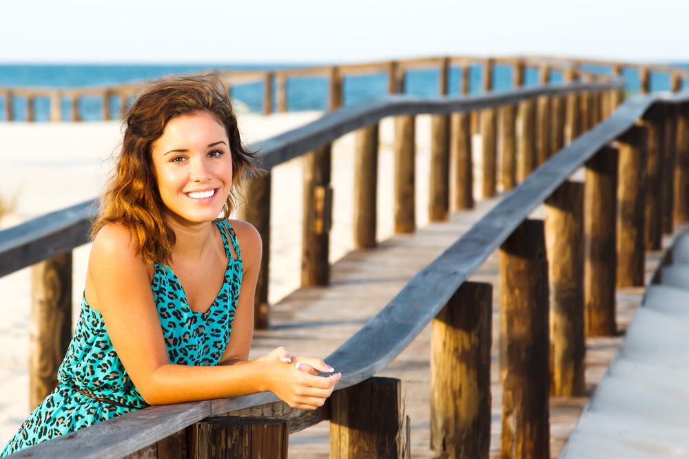 Senior posing on board walk at Kiva Dunes