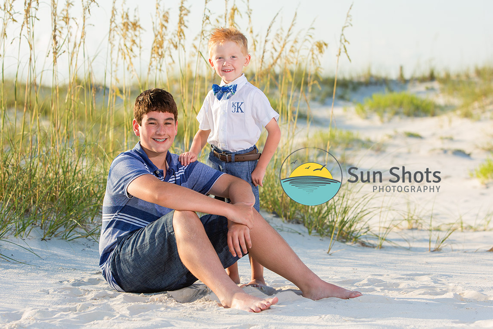 Two brothers sitting on beach for photograph