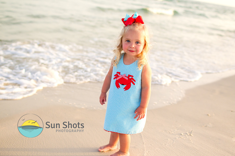 Cute girl standing by shoreline posing for picture