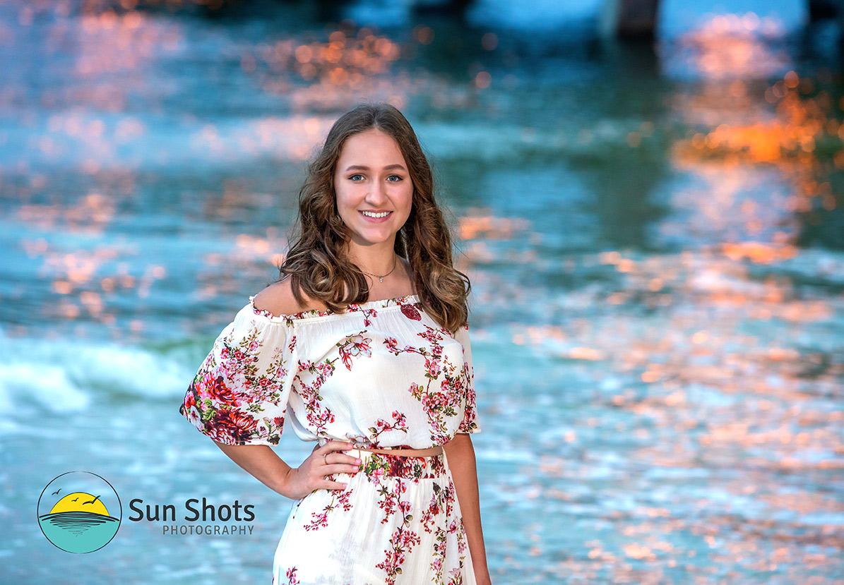 Senior portrait with ocean as backdrop.