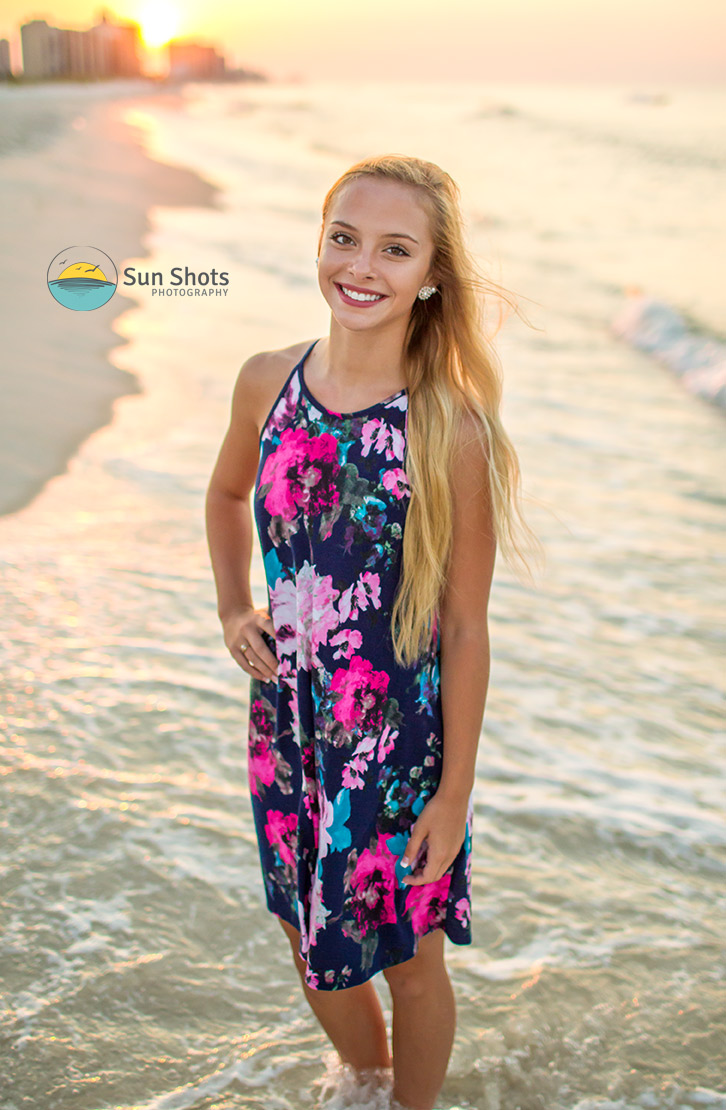 Senior portrait with sunrise in background of beach