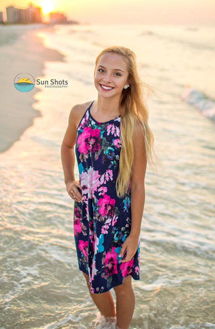 Senior portrait with sunrise in background of beach