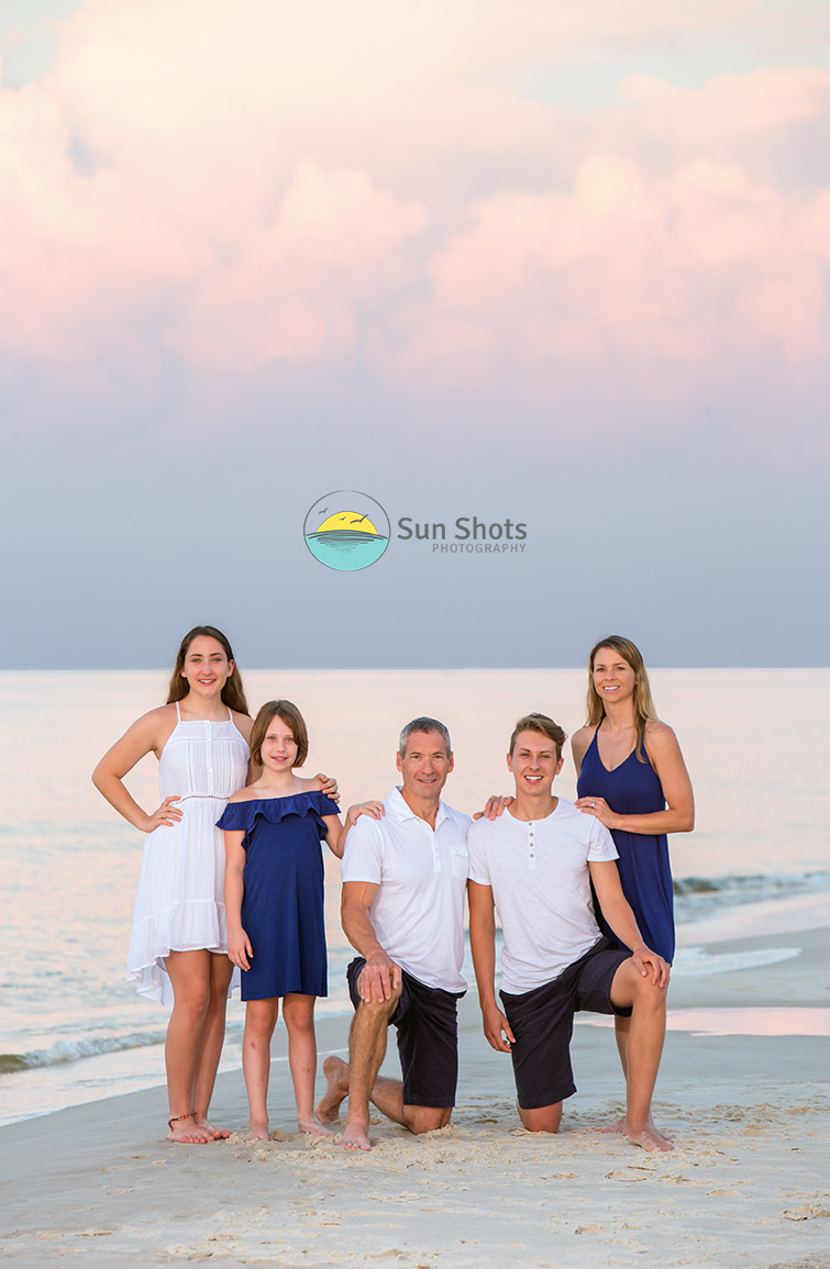 Family photograph on a beach with ocean in background