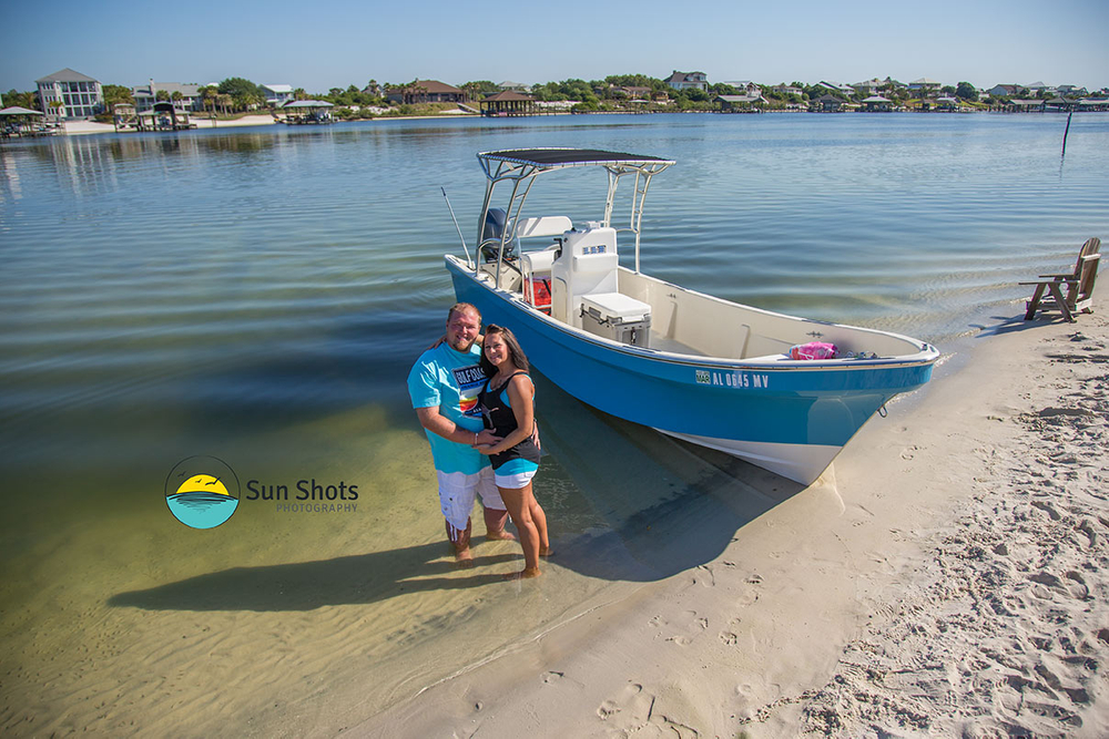 Couple taking picture on beach by boat
