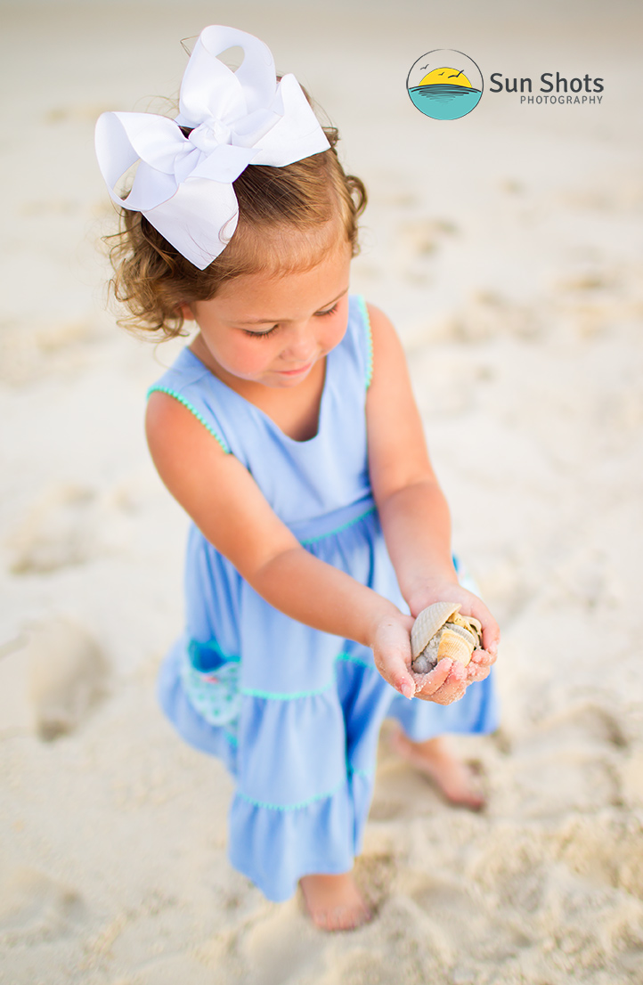Little girl holding seashells on the beach